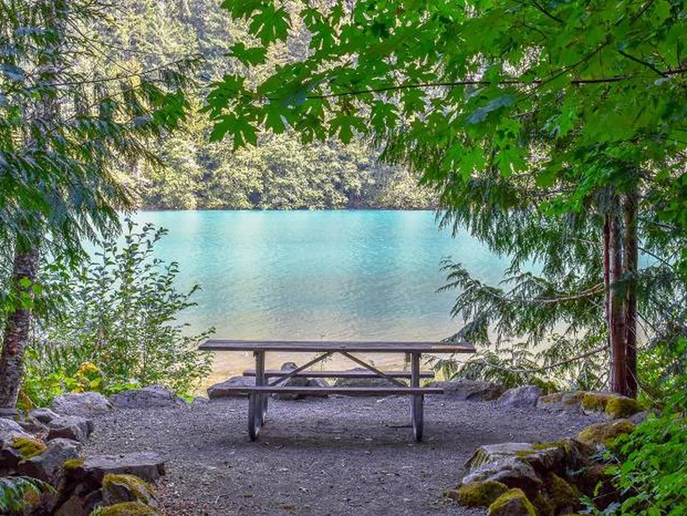 Picnic table with a view of Diablo Lake in a Colonial Creek campsite.View of Diablo Lake from a lakeside campsite at Colonial Creek South Campground.