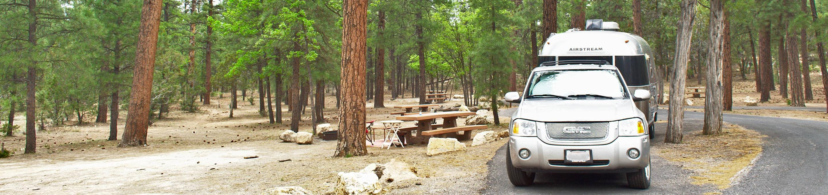 A car and trailer in the parking spot next to a picnic table and fire pit, Mather CampgroundA car and trailer in the parking spot next to a picnic table and fire pit, Aspen Loop 6 Mather Campground