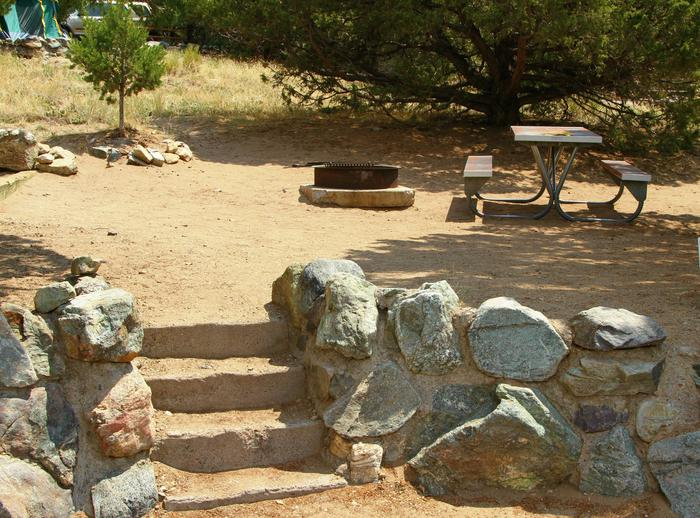Closer view of Site #84 tent pad, with stairs up from parking area, fire ring, and picnic table. Site is partially shaded by pine trees.Site #84, Pinon Flats Campground