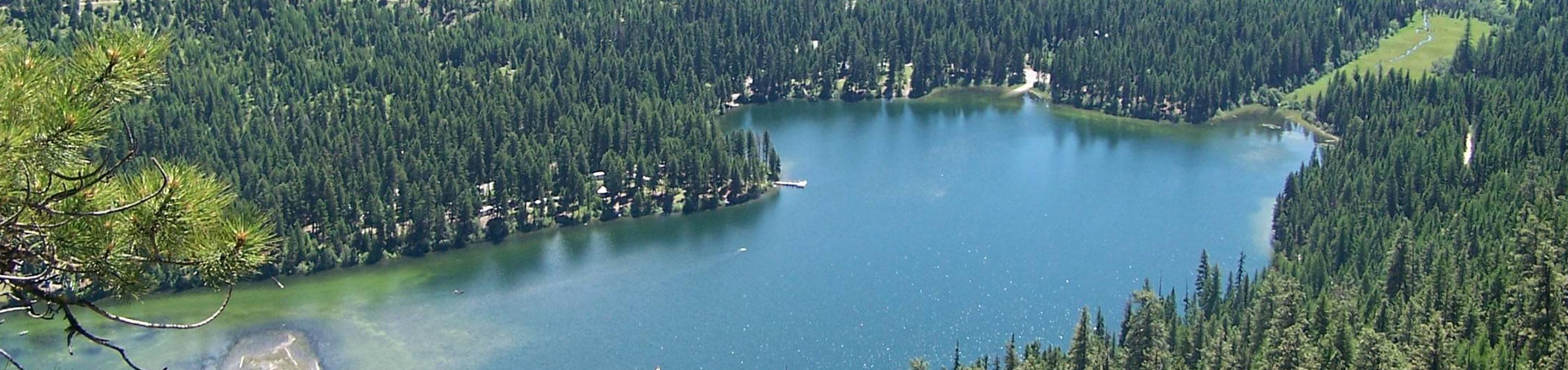 Aerial view of flat lake reflecting forested surroundings.Aerial view of Bonaparte Lake