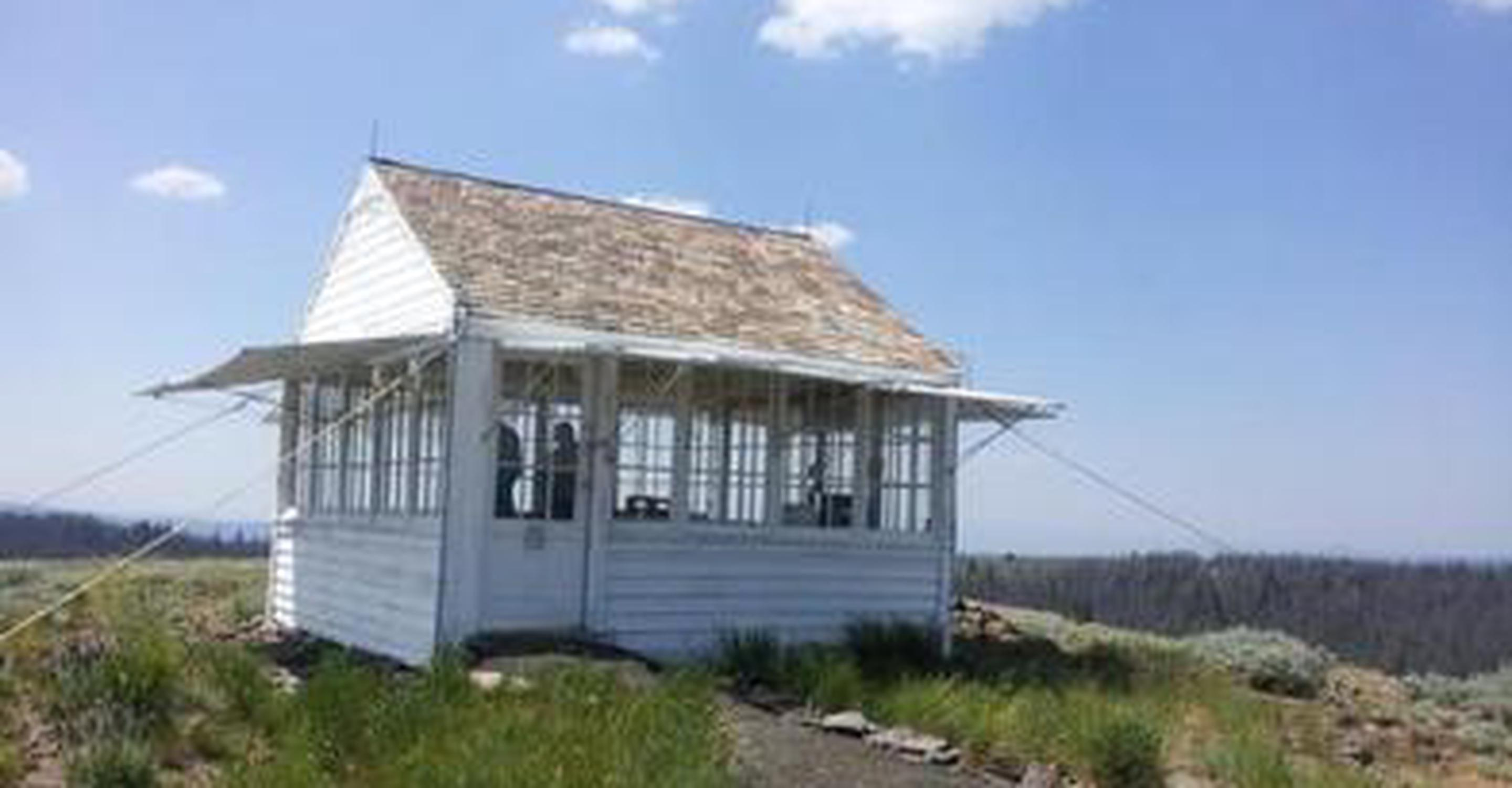 BALD BUTTE LOOKOUTLookout building with green grass, blue sky and white clouds.
