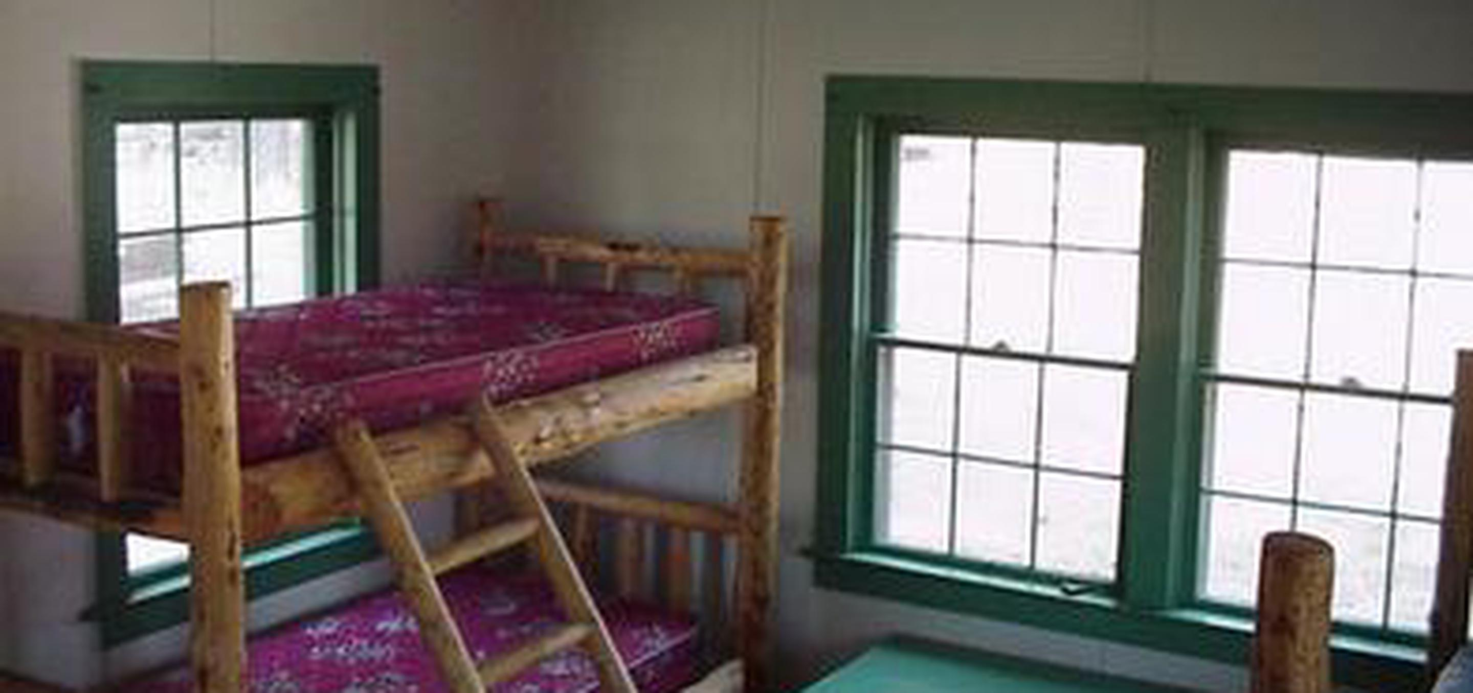 CURRIER GUARD STATIONLog bunk beds with pink mattresses in a wood paneled room painted white with three 12-pane windows with green frames.