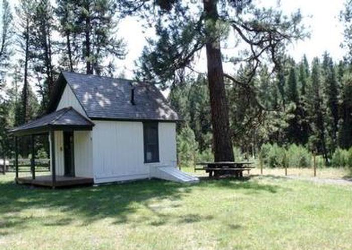 Murderers Creek Guard StationSmall white cabin in grassy field next to picnic table and large pine tree