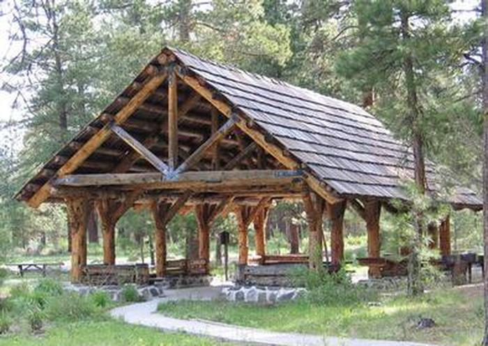 IDLEWILDLarge log framed picnic shelter next to pine trees and a grassy meadow accessed by a flat path.