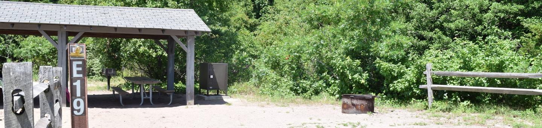 Campsite E19 incorporating a shade structure, fire ring, bbq, and food storage lockerCampsite E19