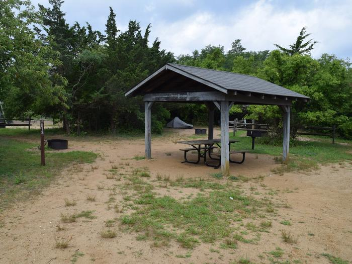 Campsite D13 incorporating a shade structure, picnic table, fire ring, BBQ, and food storage lockerD13