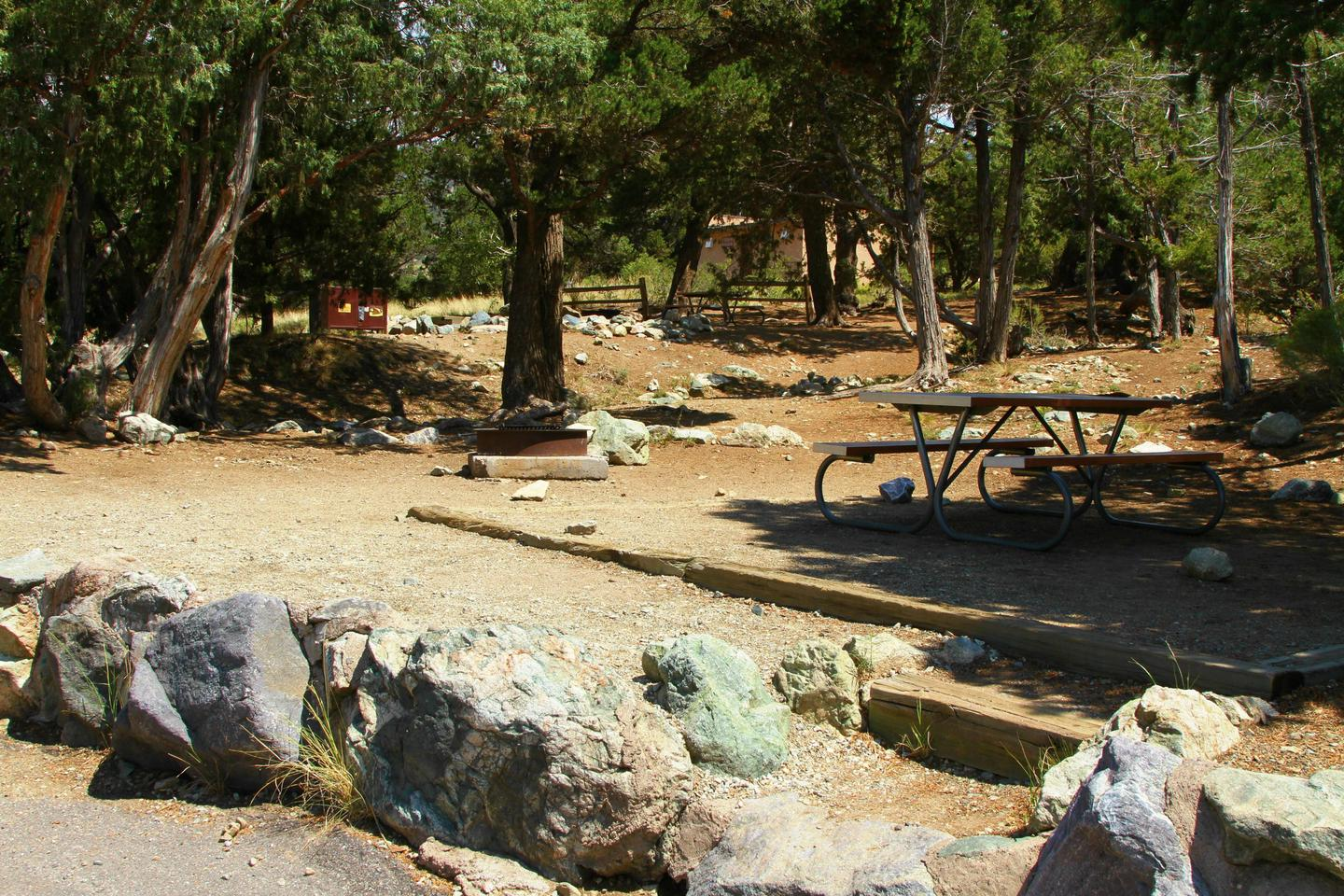 Side view of Site #29 stairs, designated tent pad, and picnic table. More trees and neighboring site #27 are in the background.Site #29, Pinon Flats Campground
