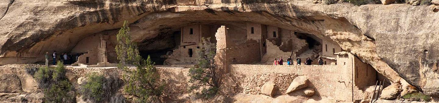 View of people exploring a cliff dwelling in cliff alcove Visitors on a ranger-guided tour of Balcony House.