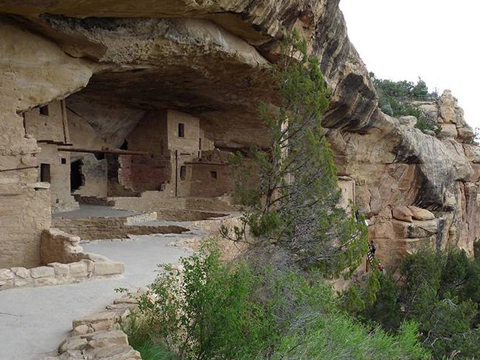 Ancient stone masonry buildings in cliff alcove with people climbing ladder in backgroundBalcony House with views of visitors climbing the ladder to enter in the background.