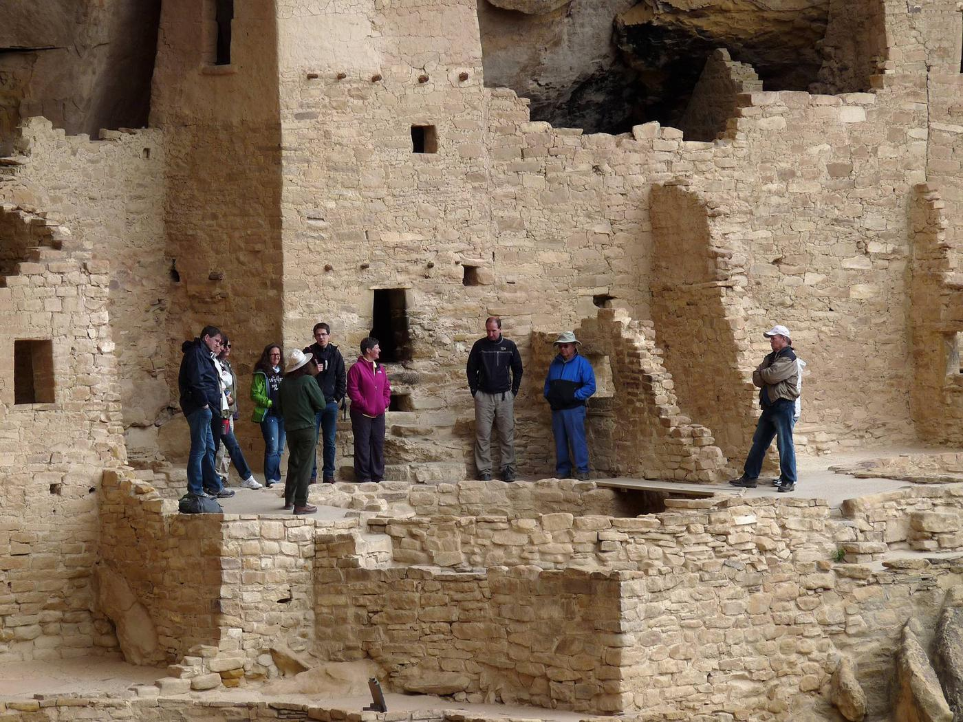 People with ranger in an ancient stone masonry villageVisitors on a ranger-guided tour of Cliff Palace.