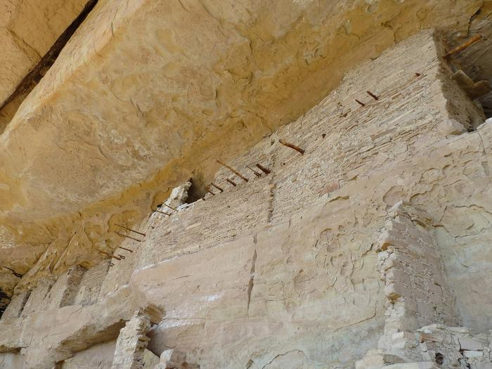 Looking up at an ancient stone masonry rooms in an alcove ledge.Spring House rooms.
