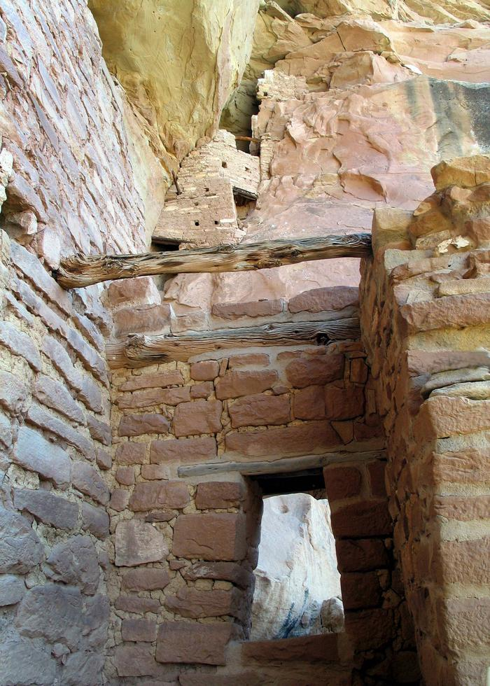 Stone masonry room with original wood beams with other rooms enclosed in a rock niche aboveIn Square Tower House looking at the Crows Nest above.