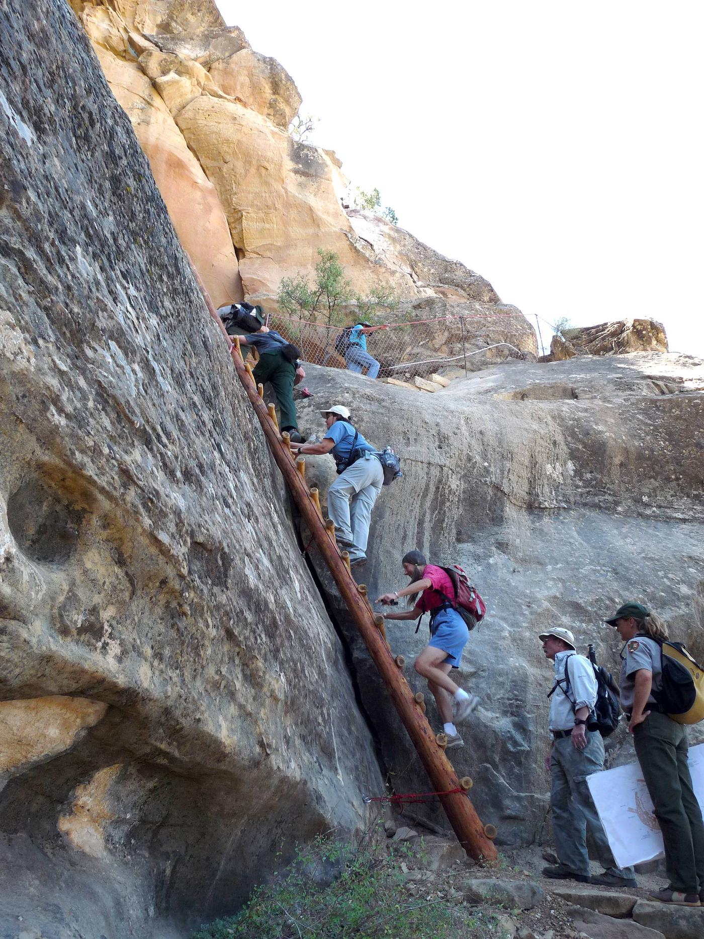 People climbing ladder and stone steps along a steep cliff faceVisitors and ranger exiting Square Tower House.