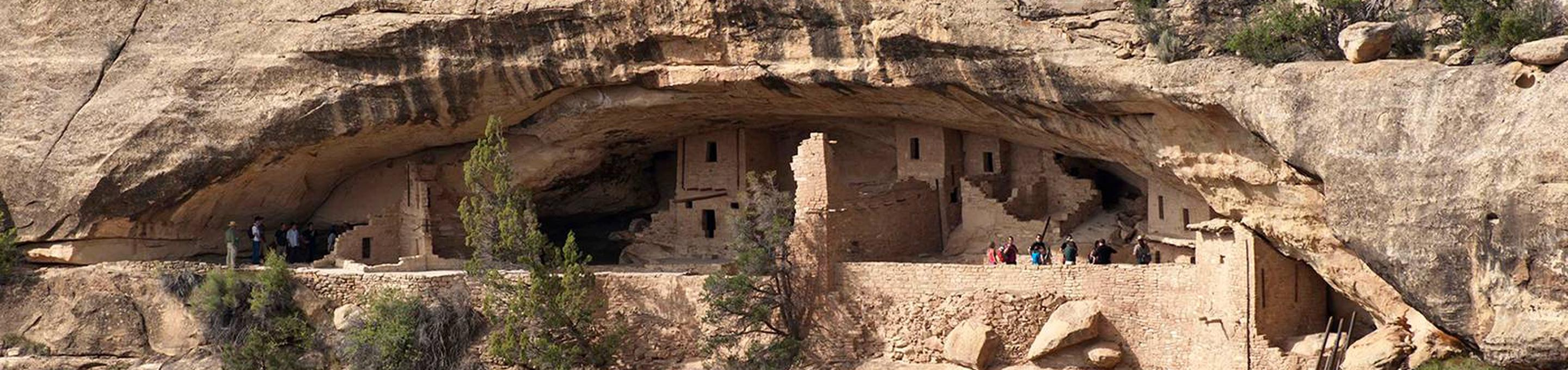 People exploring an ancient stone masonry village in a cliff alcoveVisitors on a ranger-guided tour of Balcony House.