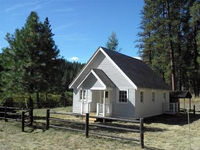 White cabin in meadow with split rail fence and pine treesSUNSHINE GUARD STATION