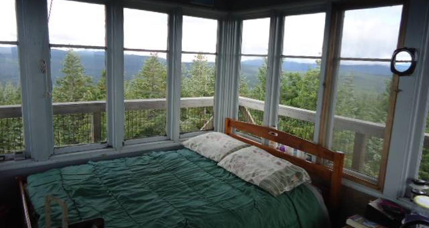 Full size bed in front of 8 window with view of mountains and trees beyond.Clear Lake Lookout sleeping area.