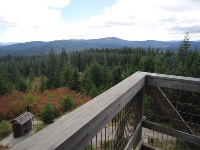 View from lookout deck over outhouse with mountains and forest in the background.View from Clear Lake Cabin Lookout.