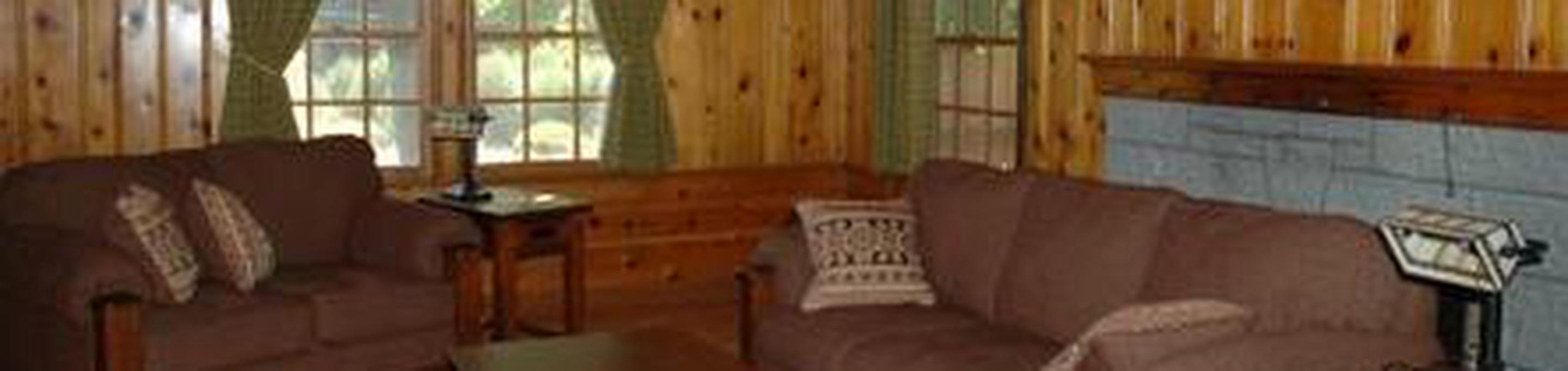Couch and love seat in wood paneled living room.Ochoco Ranger Rental Living Room