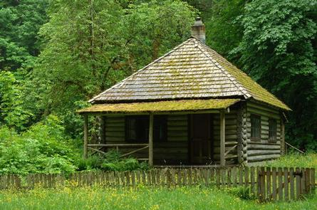 Log cabin with covered front porch in front of forest.INTERROREM CABIN