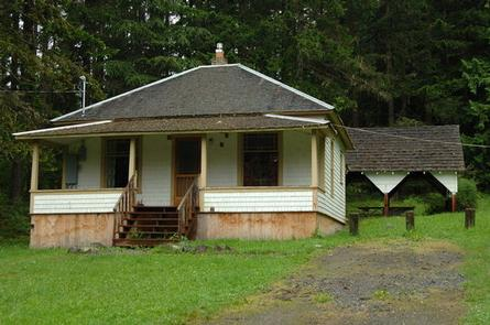 Cabin with front porch in grassy yard in front of forestLOUELLA CABIN