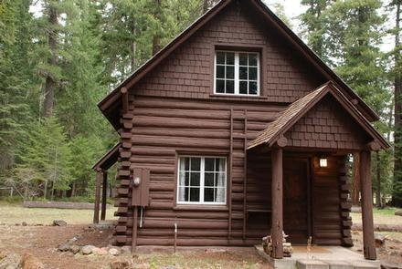 Log cabin with shake gable ends and covered entry way in conifer forestBIG ELK GUARD STATION