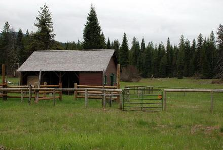 Cabin with red siding and fences in flat meadow backed by conifer forestLODGEPOLE GUARD STATION
