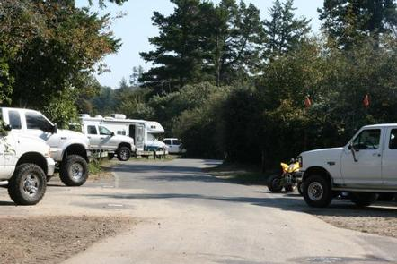 Campsite spurs along a flat paved road occupied with large white trucks, a yellow 4-wheeler and one white RV under conifer trees and blue skySPINREEL