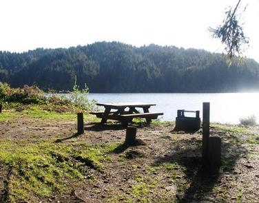 Campsite with picnic table and campfire ring overlooking lake and tree covered far shoreTAHKENITCH LANDING