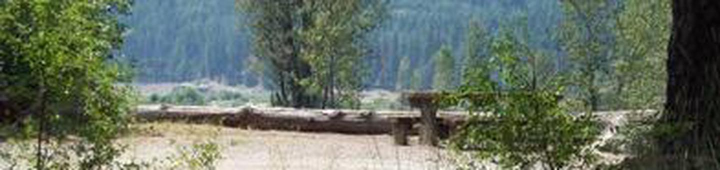 Picnic table in a flat gravel area with bushes and log parking barrier, river valley and conifer covered hills in background.CLE ELUM RIVER GROUP SITE