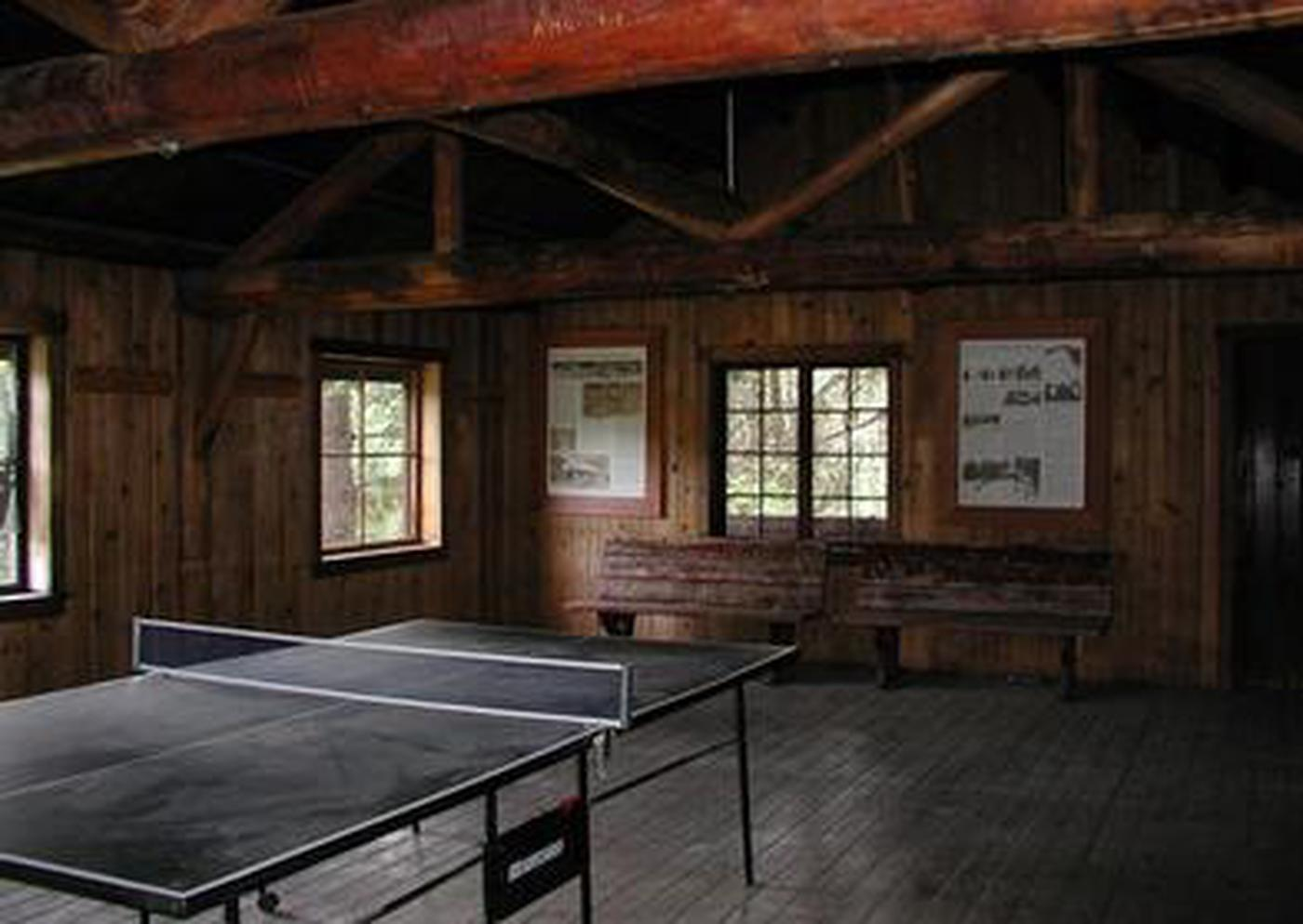Ping-pong table in dimly lit large room with log rafters and benches.Ping-Pong table in American Ridge Lodge