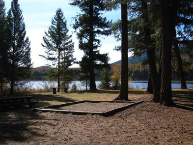 Sunlit tent pad in front of conifers in silhouette with lake and hill in background.LOST LAKE GROUP UNIT