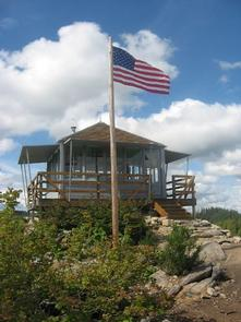 American flag flying in a stiff breeze in front of a lookout building under cloudy blue sky.GOLD BUTTE LOOKOUT