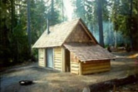 Fire ring in front of log cabin with attached, covered wood shed  in misty conifer forest.Timpanogas cabin.