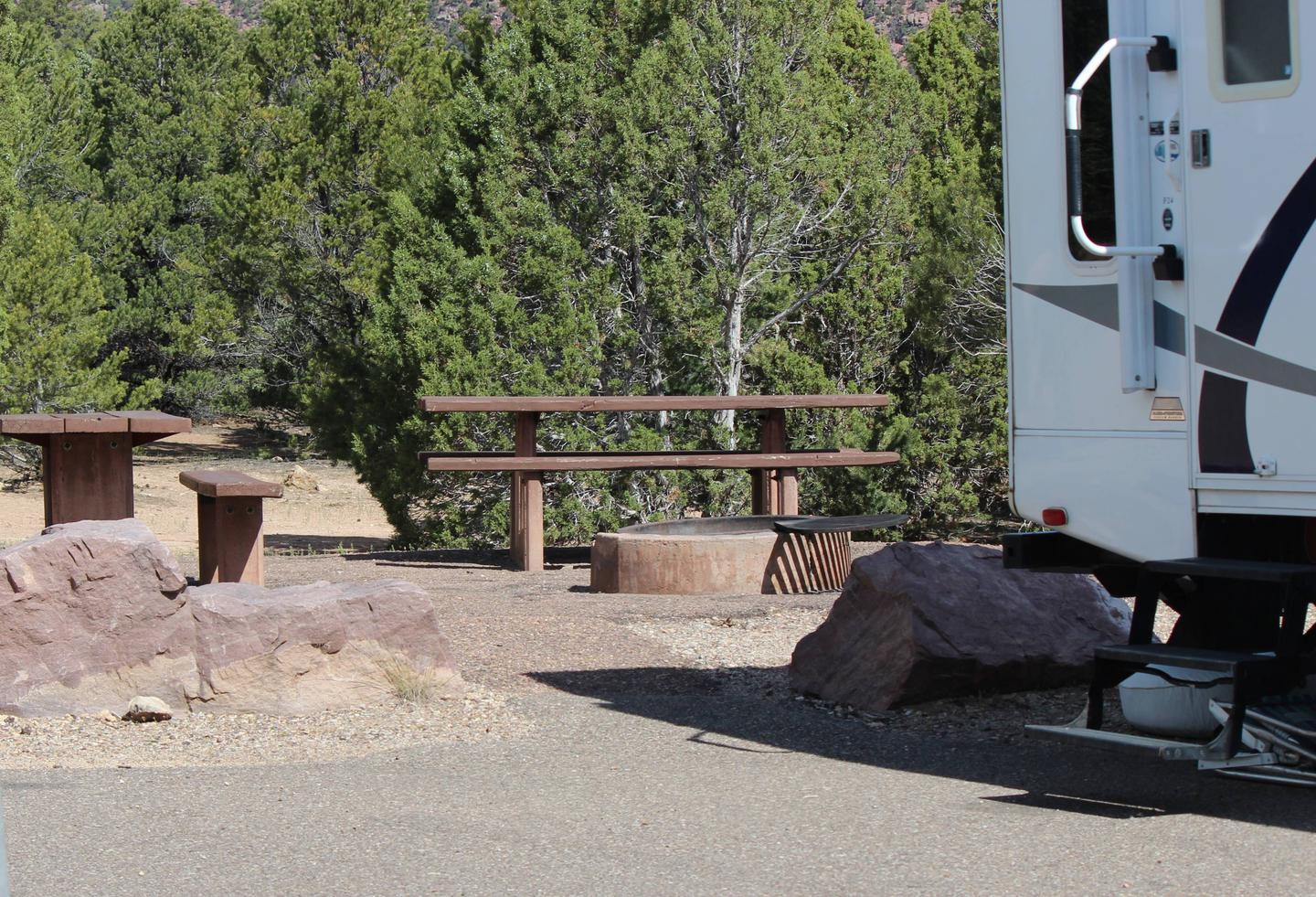 Picnic tables and fire pit behind in an area behind a travel trailer.Cedar Springs Campground: Site 6