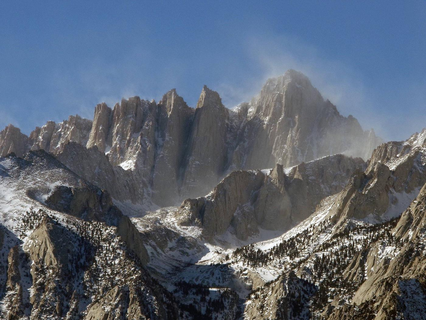 Wind blows snow from the summit of Mount Whitney. The beautiful veil of snow blowing from the summit also indicates the extreme conditions that may be encountered on Mount Whitney.