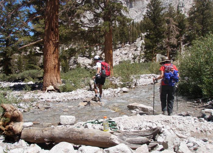 Hikers crossing stream on the Mount Whitney Trail.Wilderness hikers encounter a stream crossing.