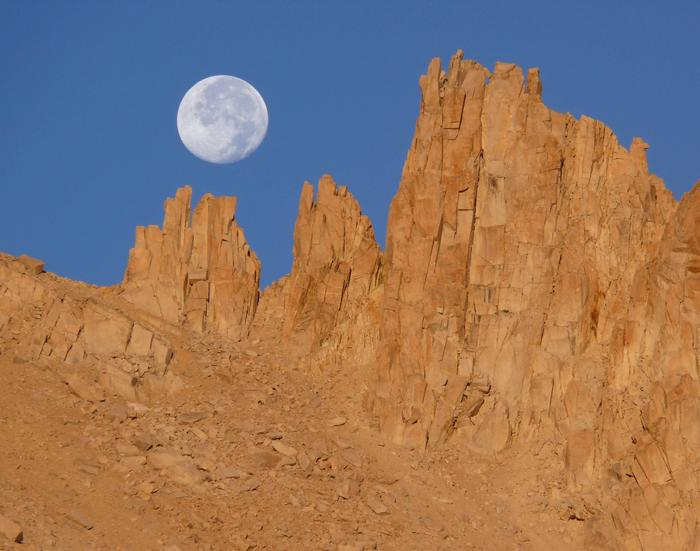 Full moon sets over pinacles of the Sierra Crest.Dawn light illuminates the Sierra Crest as a full moon sets.
