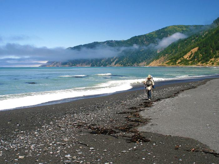 A backpacker walks along the beach in the King Range National Conservation Area.King Range National Conservation Area