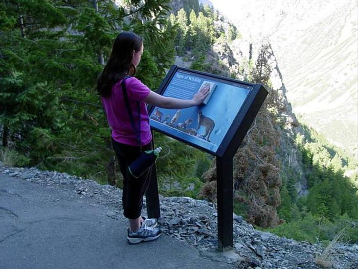 Young woman places hand on cougar paw print signWayside Sign on cave trail