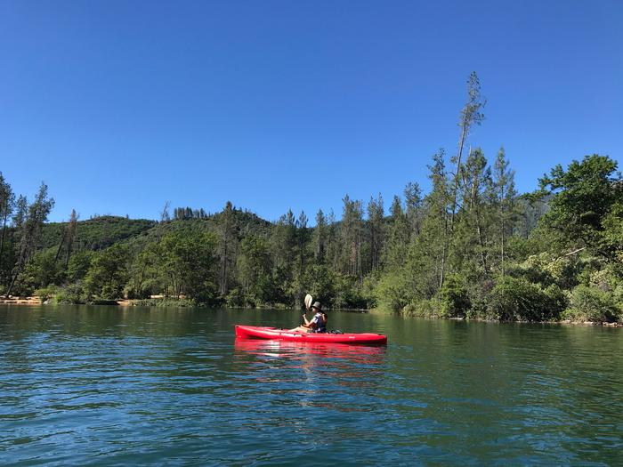 A bright red kayak under a cloudless blue sky along a wooded shore.Ranger leading a kayak tour on Whiskeytown Lake