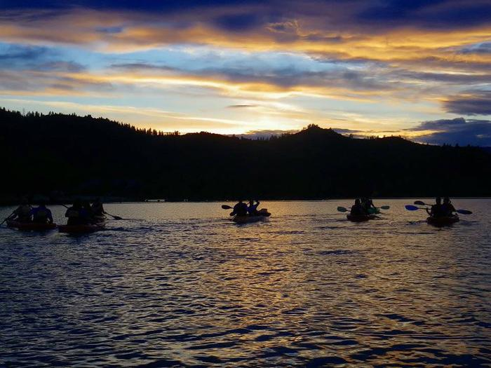 Kayakers are silhouetted against the setting sun as they head out on a moonlight tour.Moonlight kayak tour on Whiskeytown Lake