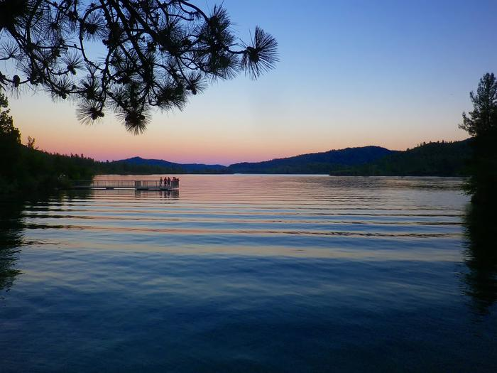 Silhouettes of surrounding mountains and trees frame a sunset scene along Whiskeytown Lake.Whiskeytown Lake at sunset