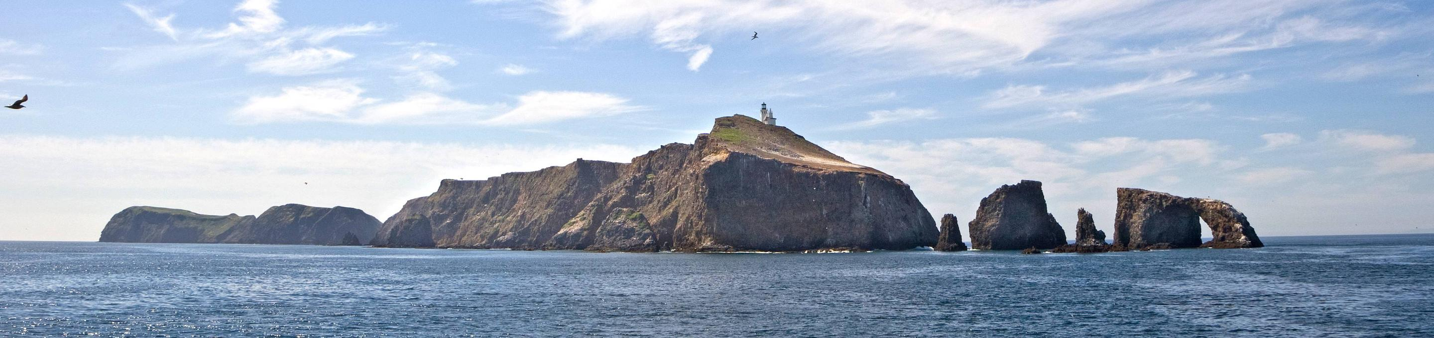 Small island with arch rock and lighthouse on top.Channel Islands National Park