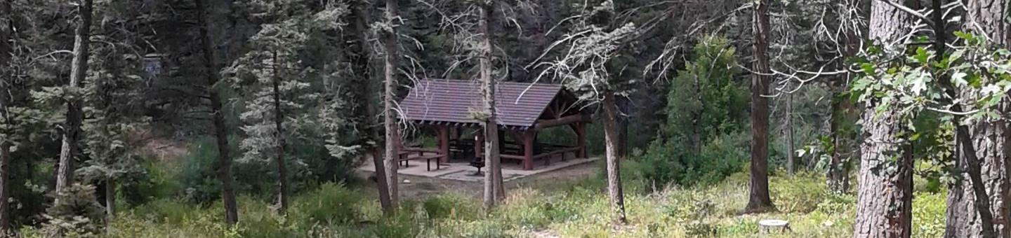 This is a picture of a pavilion in the trees Balsam Glade Group Site Pavilion