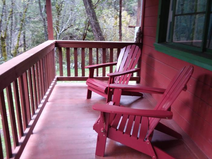 Front porch and two red Adirondack of red cabin.Enjoy sitting out under covering on the front porch of the historic Forest Glen Guard Station.