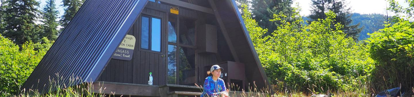 Woman sitting on porch of SHAKES SLOUGH 2 CABINShakes Slough 2 Cabin