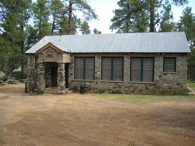 Schoolhouse rock sided exterior with four screened windows and covered thresh hold with two stairs on the right side.Groom Creek Schoolhouse
