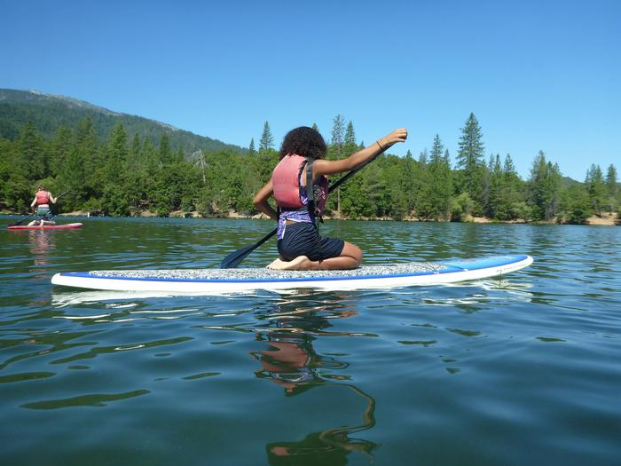Two paddle boarders sitting on their boards while paddling on Whiskeytown LakeWhiskeytown Paddleboarding
