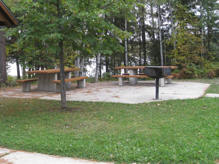 Picture of picnic tables and grills.Picnic area with tables and grills.  Picnic site is located adjacent to parking area and near beach and play area.