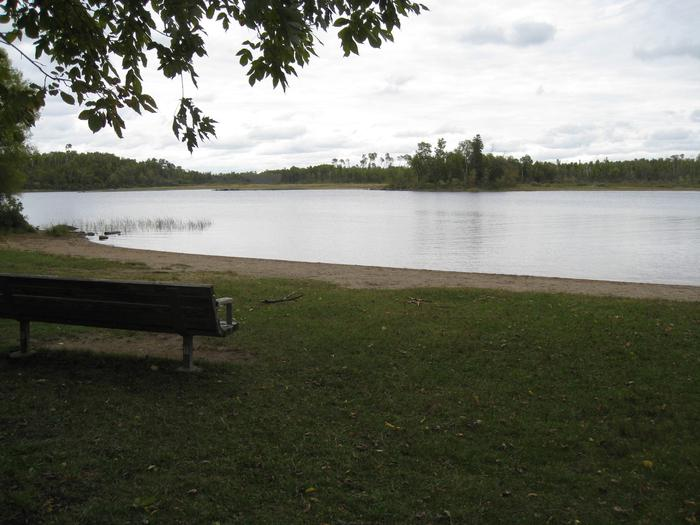 Picture of beach and bench.Fall Lake Beach Area.  Area contains benches and sand beach.  Located near play area and picnic sites.